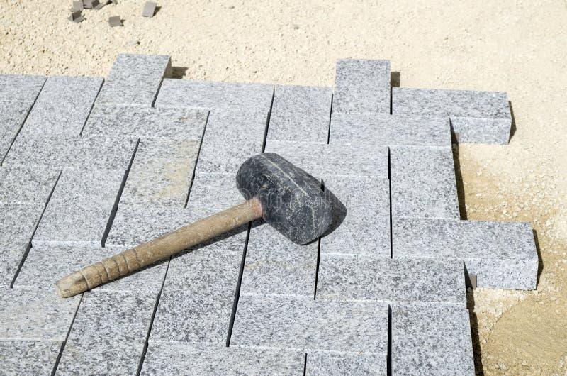 Mazo de goma en un nuevo pavimento del granito fotos de archivo