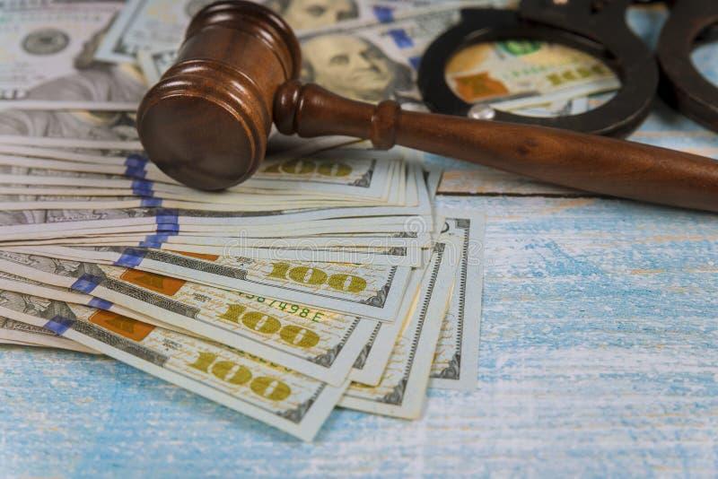 Mazo del martillo del juez con las esposas en los billetes de dólar fotos de archivo