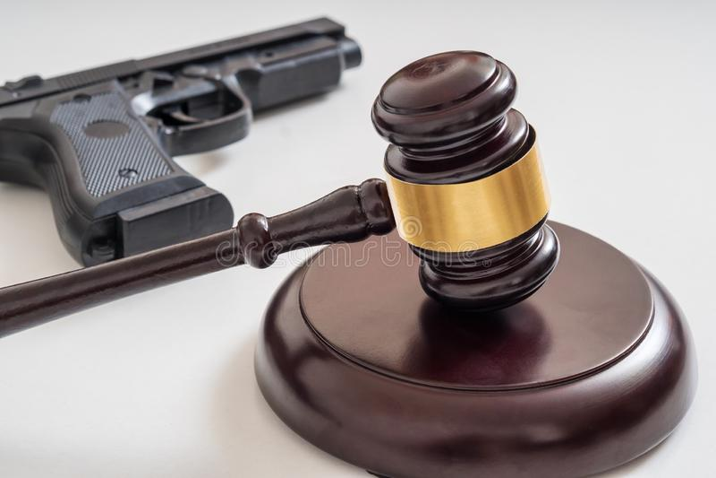Mazo delante de una pistola Leyes del arma y concepto de la legislación imagenes de archivo