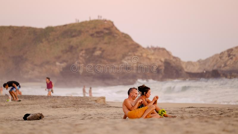 Couple chilling out during sunset at Mermejita beach. Mazunte, Oaxaca, Mexico - January, 24th, 2018: couple laying during sunset at Mermejita beach stock image
