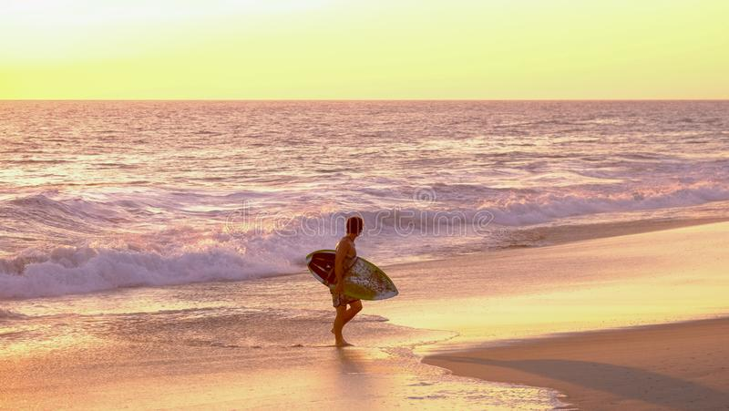 Surfer at sunset at Mermejita beach. Mazunte, Oaxaca, Mexico - January, 24th, 2018: sufer coming out the water during sunset at Mermejita beach stock photo