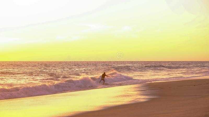 Surfer at sunset at Mermejita beach. Mazunte, Oaxaca, Mexico - January, 24th, 2018: surfing at the shore during sunset at Mermejita beach royalty free stock photo