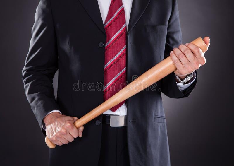 Mazza da baseball della tenuta dell'uomo d'affari immagine stock