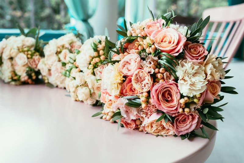 Mazzi di nozze della sposa e delle damigelle d'onore sulla tavola prima del ceremo immagine stock libera da diritti