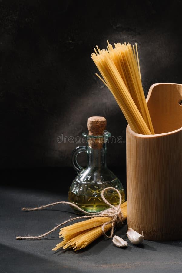 mazzi di spaghetti crudi con aglio e la bottiglia di olio d'oliva fotografia stock libera da diritti