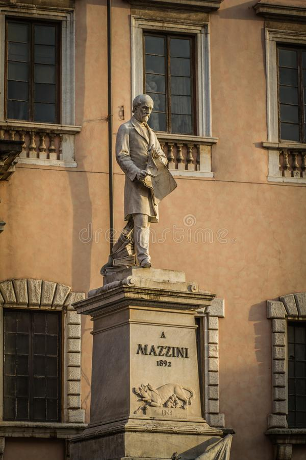 Mazzini Statue in Carrara, Tuscany, Italy. Marble statue of Mazzini with a newspaper in his hands. On the pedestal is a relief of the Capitoline Wolf, with the royalty free stock photography
