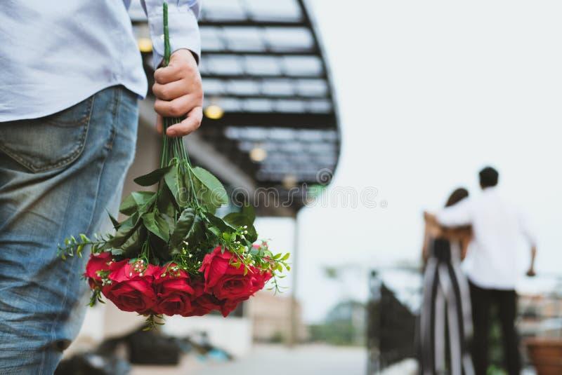 Mazzo affranto della tenuta dell'uomo delle rose rosse che ritengono triste mentre s immagine stock libera da diritti