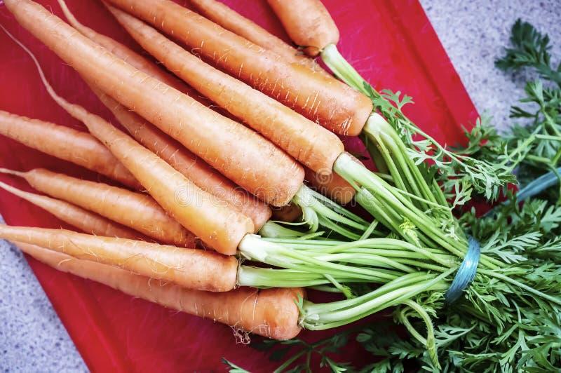 Mazzo appetitoso di carote crude fresche legate con corda su un tagliere rosso Vista superiore fotografie stock