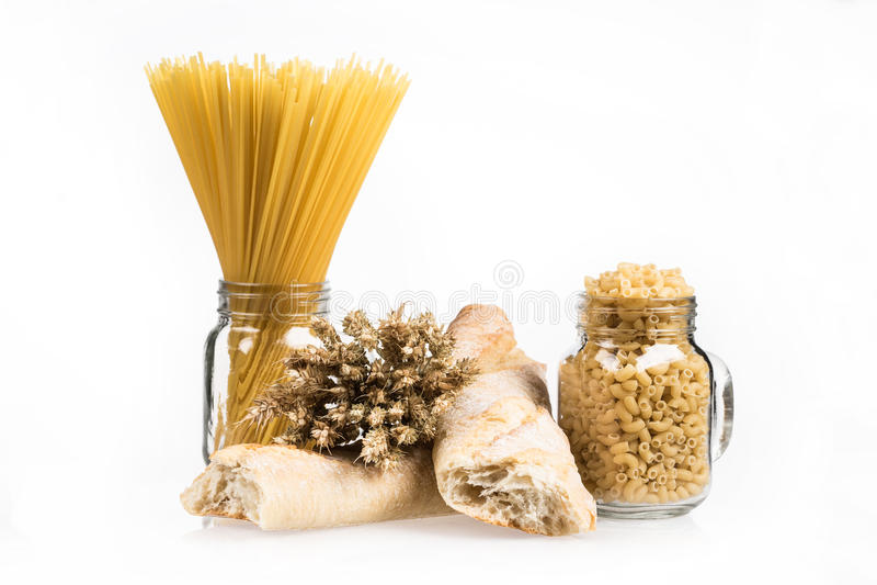Mazzo, baguette, maccheroni e pasta del grano in barattolo, su fondo bianco Mazzo e pane del grano Spighette dorate Alimento immagine stock