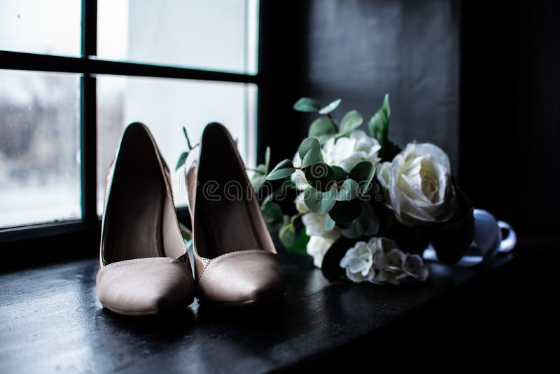 Mazzo bianco di nozze e scarpe rosa della sposa vicino alla finestra fotografia stock libera da diritti