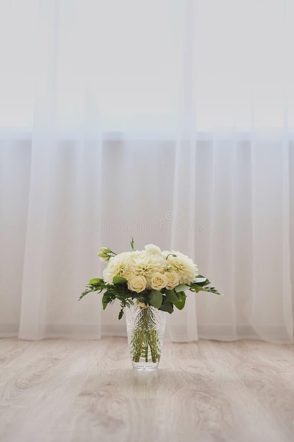 Mazzo bianco in un vaso di vetro da stare davanti ai precedenti del tessuto per la sposa nella cerimonia di nozze immagine stock