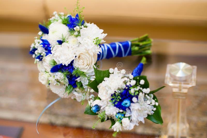 Mazzo blu e bianco di nozze delle rose sulla tavola di vetro immagine stock