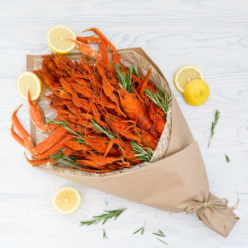 Mazzo che consistono dei gamberi e dei granchi bolliti con i ramoscelli dei rosmarini e fette del limone su una tavola di legno b fotografie stock