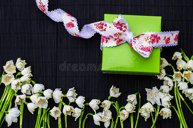 Mazzo dei bucaneve nella primavera con un regalo immagini stock