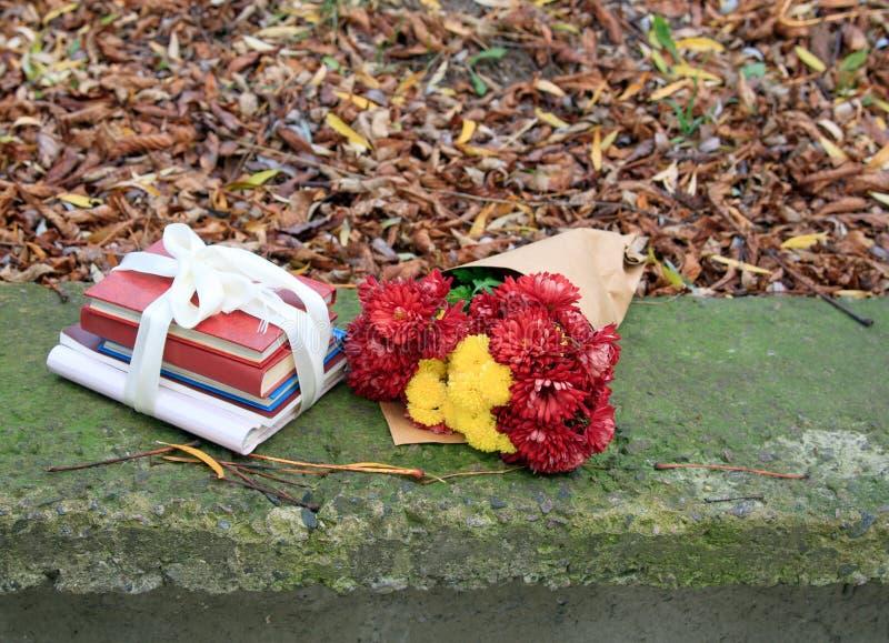 Mazzo dei crisantemi e una pila di libri immagini stock