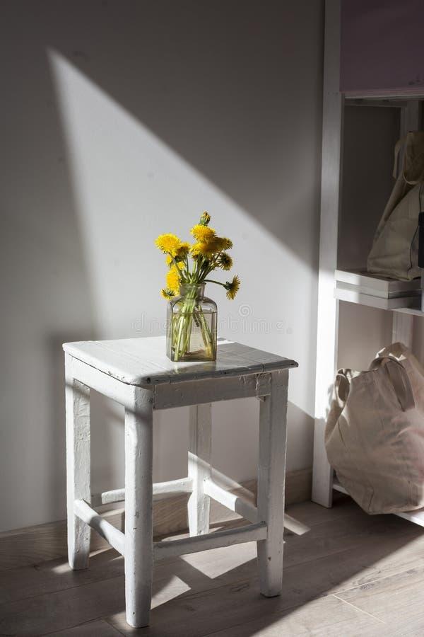 Mazzo dei denti di leone gialli in un barattolo trasparente di vetro su un panchetto di legno bianco contro lo sfondo della paret fotografia stock