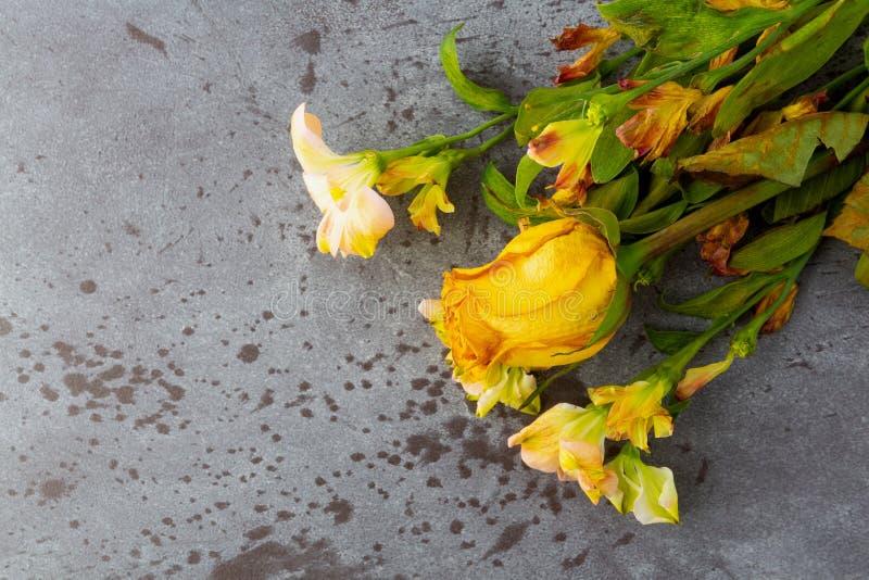 Mazzo dei fiori appassenti con una singola rosa gialla su un fondo grigio fotografia stock