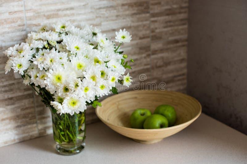 Mazzo dei fiori bianchi e delle mele su un piatto fotografia stock