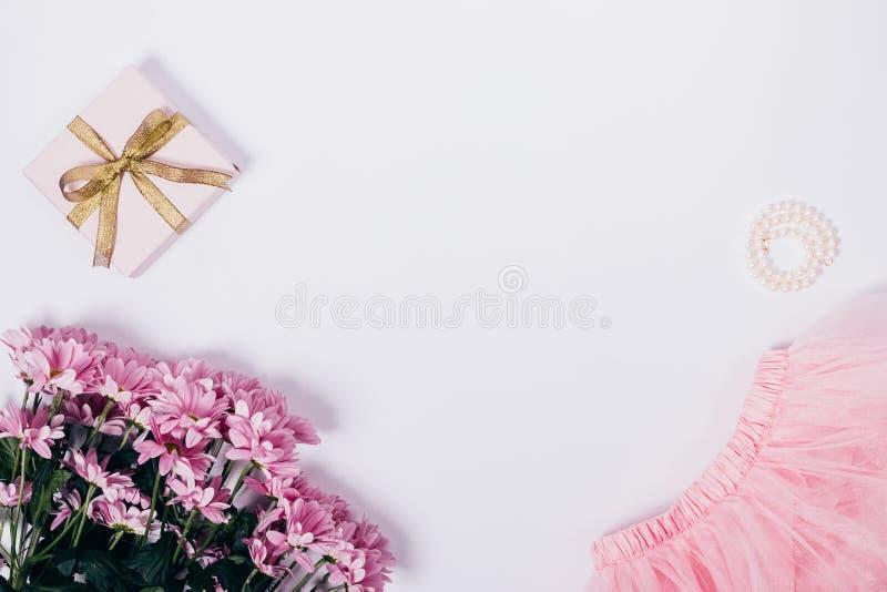 Mazzo dei fiori, della gonna rosa, del contenitore di regalo e delle perle immagine stock