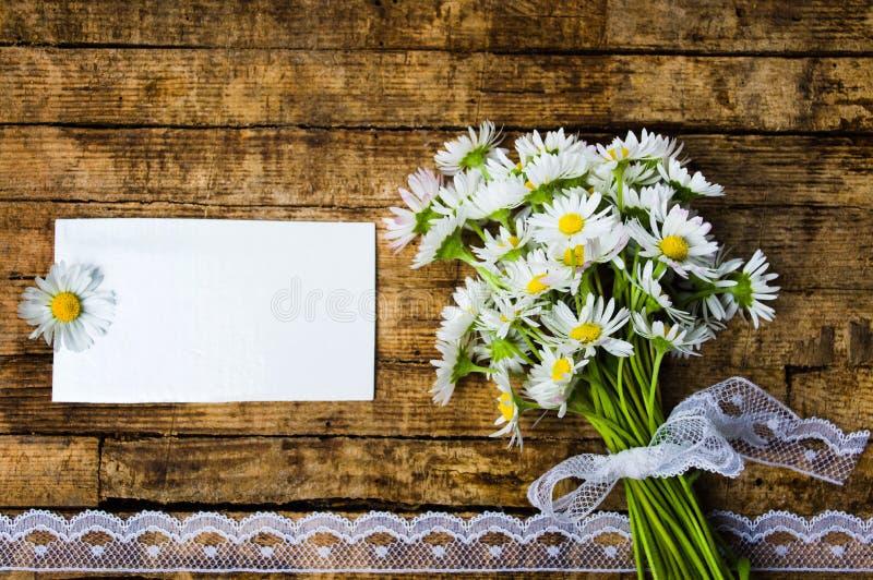 Mazzo dei fiori della margherita con la carta vuota fotografie stock