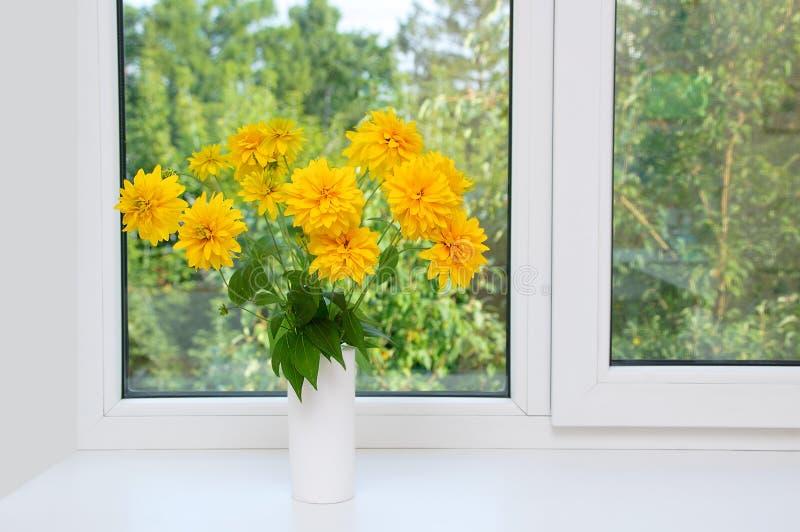 Mazzo dei fiori gialli di Heliopsis in un vaso bianco sulla finestra fotografia stock libera da diritti