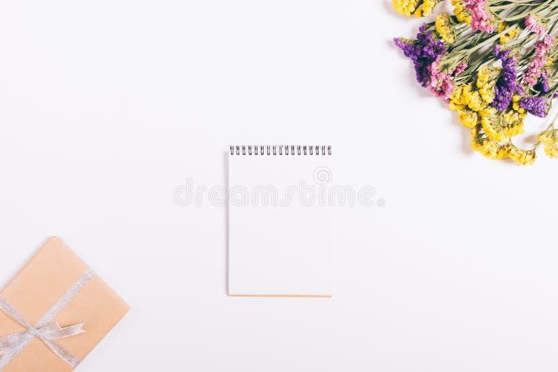 Mazzo dei fiori variopinti, del taccuino e della scatola con una menzogne del regalo fotografia stock