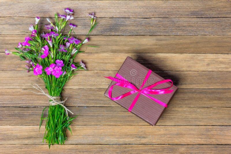 Mazzo dei garofani e della scatola marrone con un regalo su un fondo di legno immagini stock