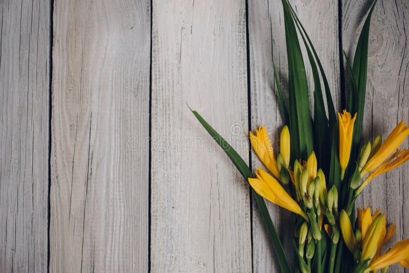 mazzo dei gigli gialli su un fondo di legno, mazzo di nozze immagini stock libere da diritti