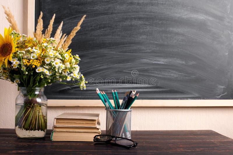 Mazzo dei libri e dei wildflowers dell'insegnante di vetro sulla tavola, sulla lavagna del fondo con gesso Il concetto del giorno immagine stock libera da diritti