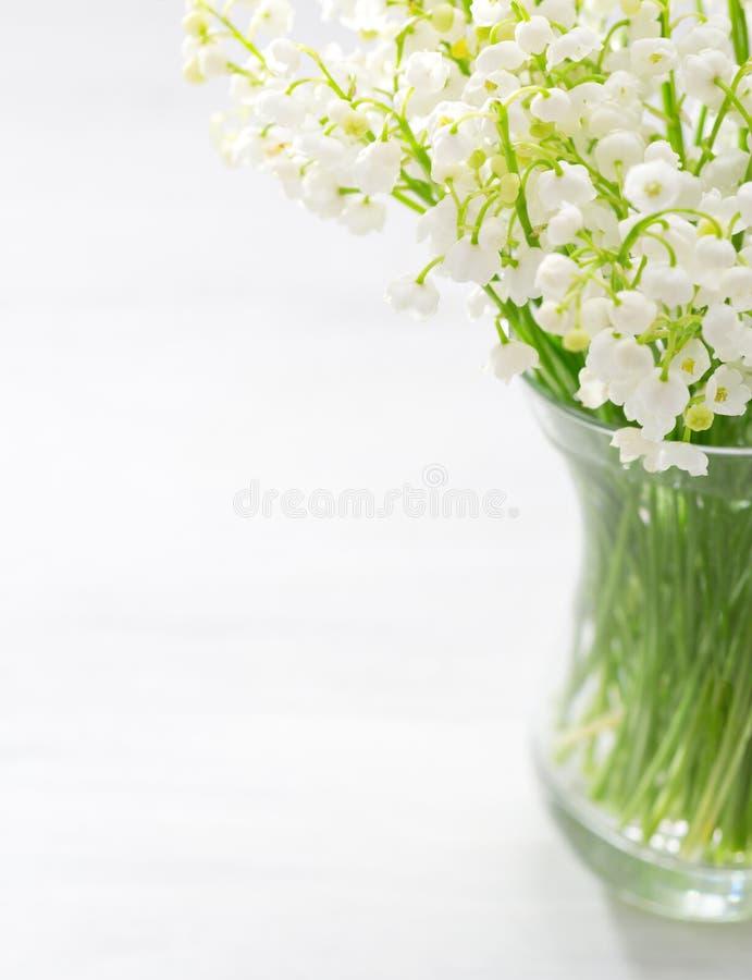 Mazzo dei mughetti in vaso di vetro fotografia stock