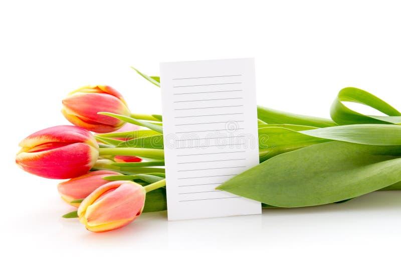 Mazzo dei tulipani con una carta del messaggio fotografia stock libera da diritti
