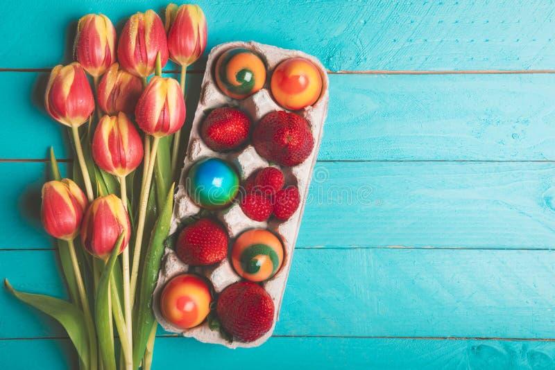 Mazzo dei tulipani ed uova di Pasqua sulla tavola blu fotografia stock
