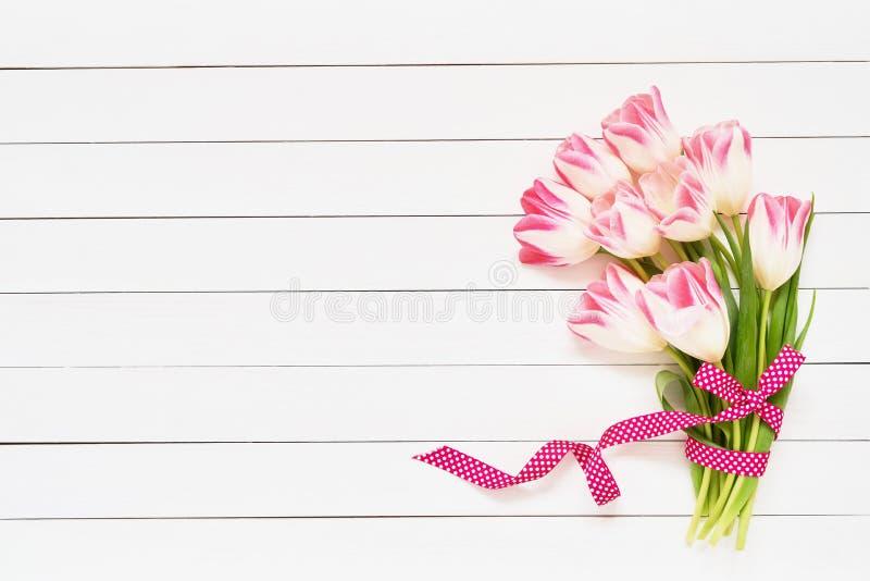 Mazzo dei tulipani rosa decorati con il nastro su fondo di legno bianco Vista superiore, spazio della copia Cartolina d'auguri fotografie stock
