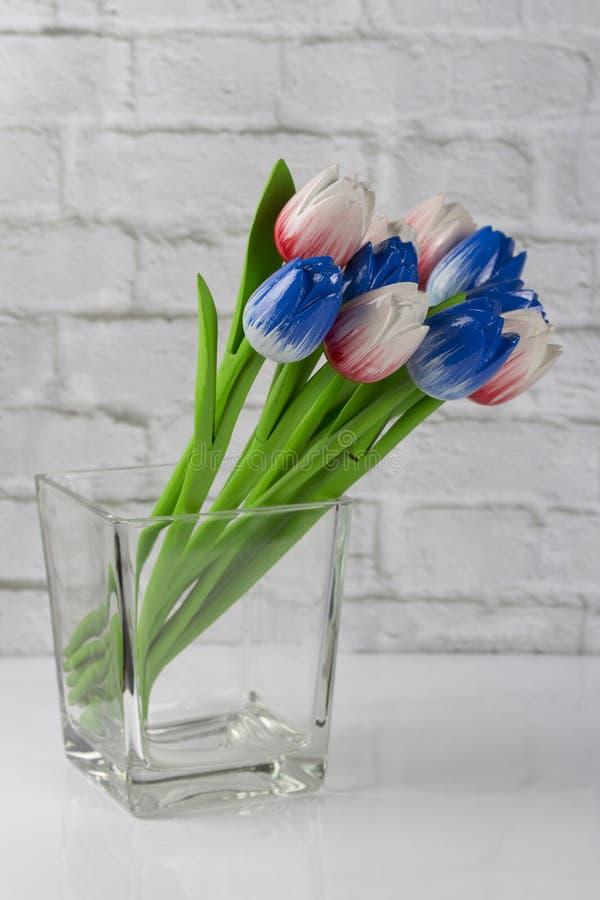 Mazzo dei tulipani rossi blu di legno in un vaso trasparente fotografia stock libera da diritti
