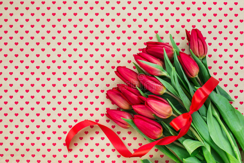 Mazzo dei tulipani rossi sugli ambiti di provenienza dei cuori Copi lo spazio fotografie stock libere da diritti