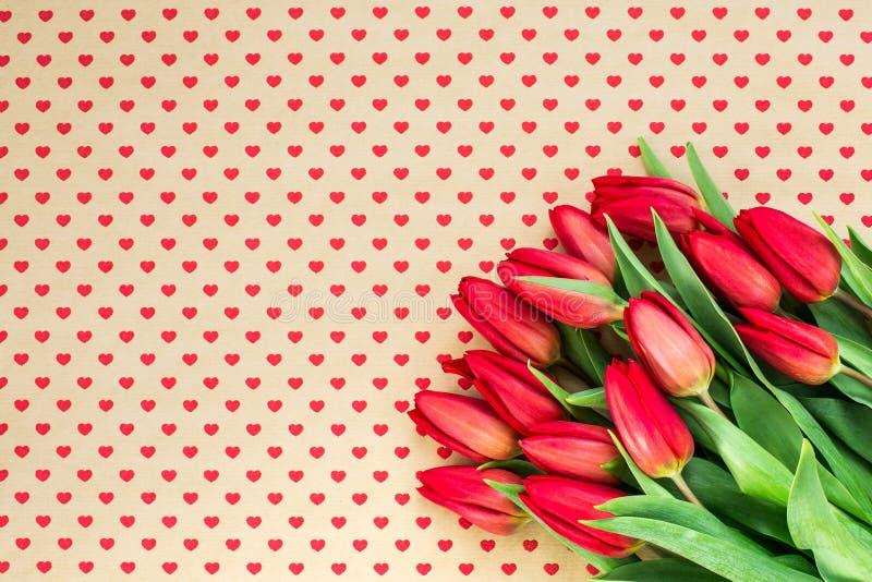 Mazzo dei tulipani rossi sul fondo dei cuori Copi lo spazio, fotografia stock libera da diritti