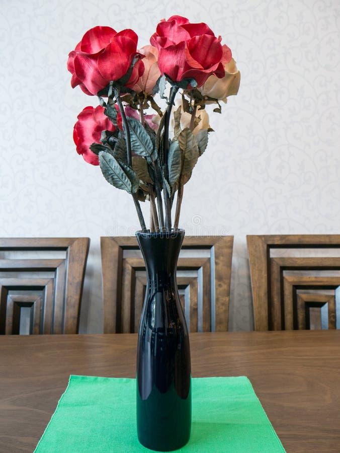 Mazzo del fiore artificiale della rosa rossa in vaso immagini stock libere da diritti