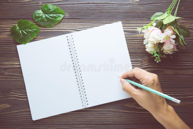 Mazzo del fiore con scrittura della mano sulla tavola di legno rustica del taccuino vuoto del diario con lo spazio della copia, m fotografie stock libere da diritti