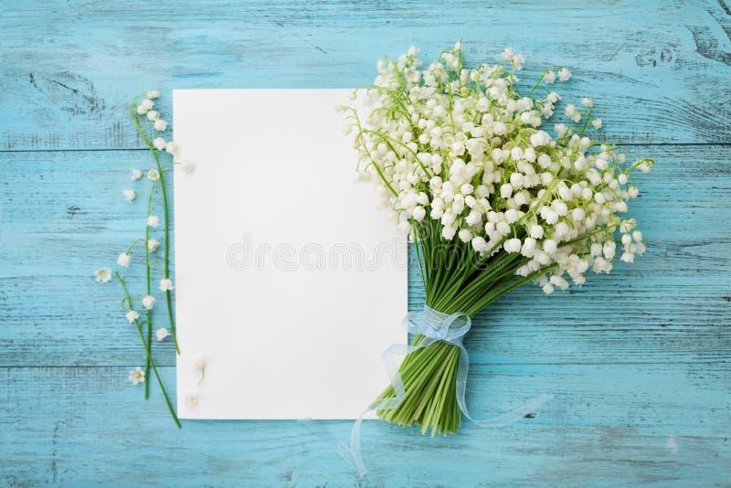 Mazzo del mughetto dei fiori e dello strato di carta vuoto sulla tavola rustica del turchese da sopra, bella carta d'annata, vist fotografia stock libera da diritti
