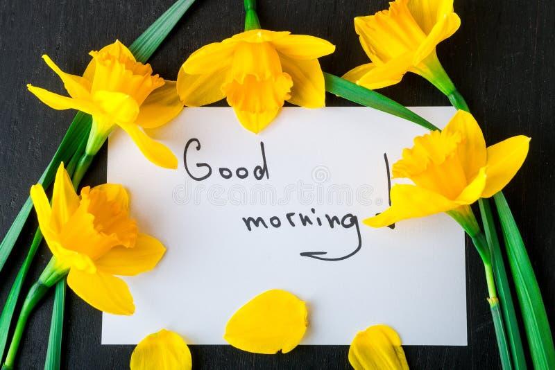 Mazzo del narciso vicino alla carta con il buongiorno su fondo nero Vista superiore Copi lo spazio Giorno di madri o il giorno de fotografie stock libere da diritti