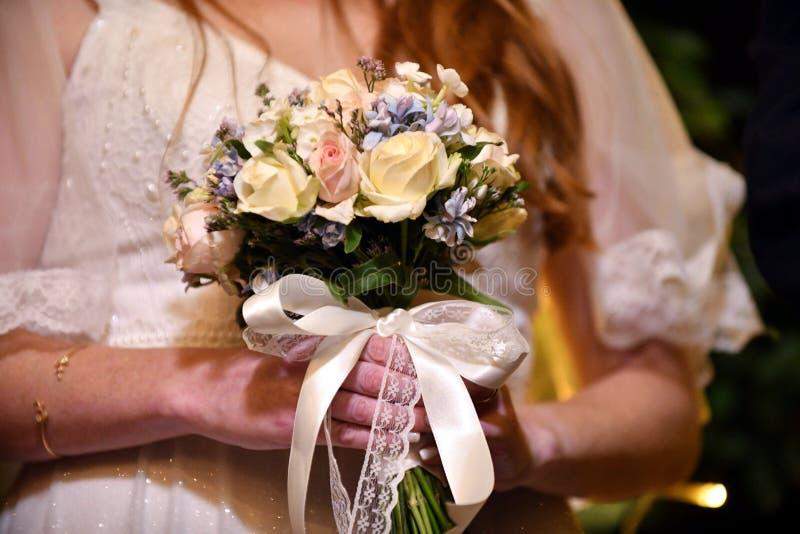 Mazzo delicato adorabile di nozze nei colori gialli e blu nelle mani della sposa fotografia stock libera da diritti