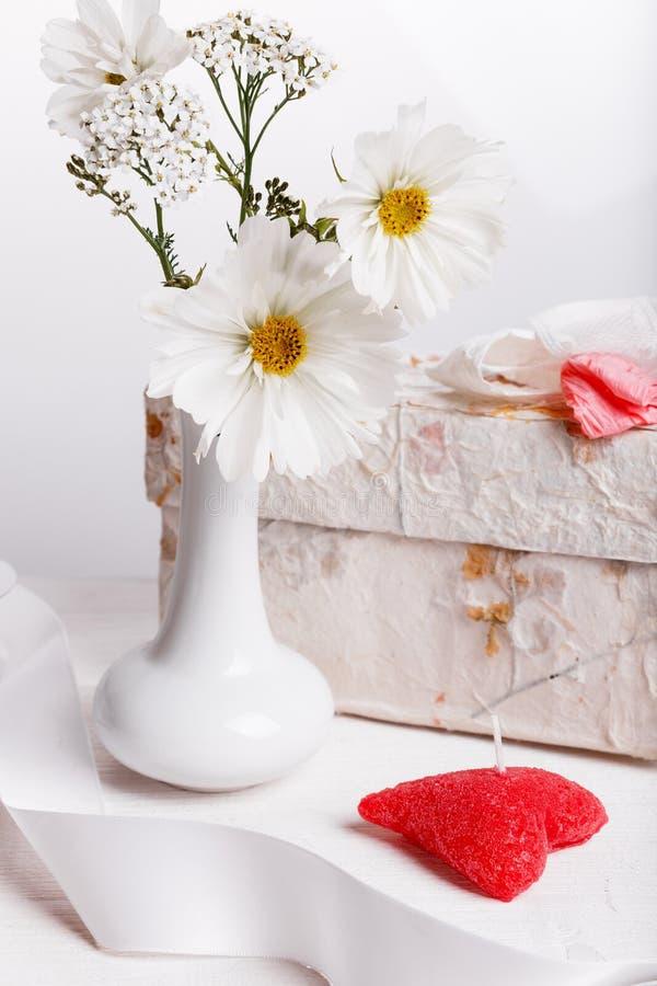 Mazzo dell'universo o del cosmea bianco dei wildflowers in vaso bianco, regalo, candela rossa sotto forma di cuore Cartolina d'au fotografia stock
