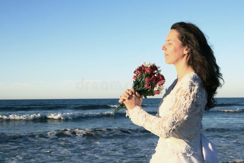 Mazzo della holding della sposa dall'oceano immagine stock