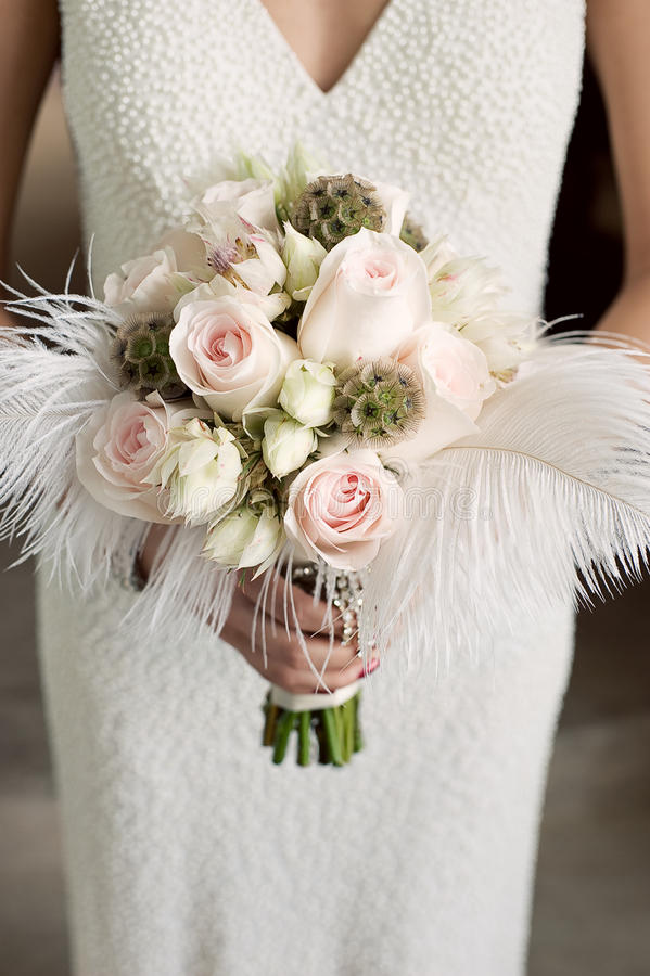 Mazzo della holding della sposa delle rose con le piume fotografia stock