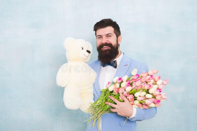 Mazzo della sorgente 8 di marzo uomo barbuto in cravatta a farfalla con i fiori del tulipano ami la data con i fiori Buon complea immagini stock