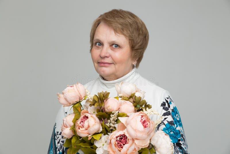 Mazzo della tenuta della signora anziana dei fiori a disposizione immagini stock