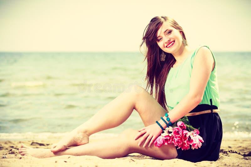 Download Mazzo Della Tenuta Della Donna Dei Fiori Che Si Siedono Sulla Spiaggia Immagine Stock - Immagine di bianco, romantico: 117981965