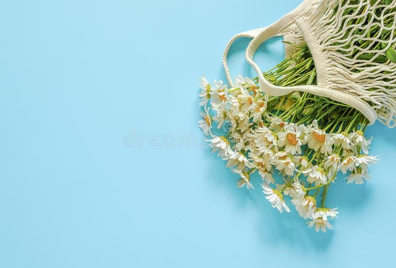 Mazzo delle margherite del campo nella borsa di compera riutilizzabile della maglia di eco su fondo blu Concetto nessuno spreco d fotografie stock