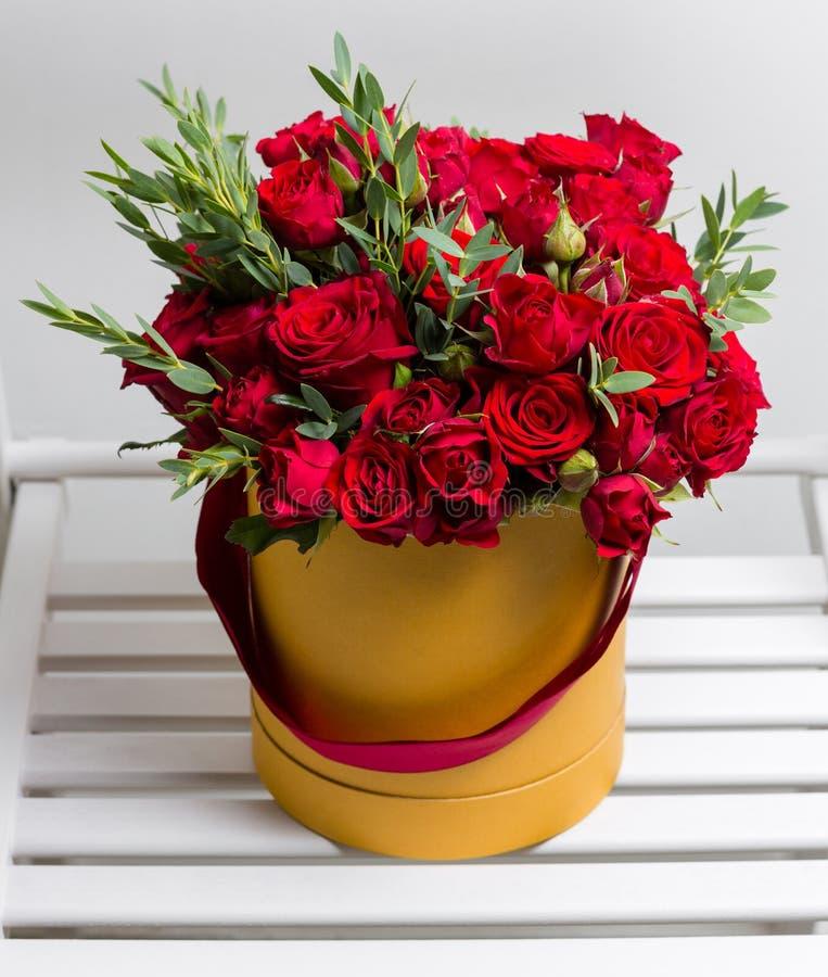 Mazzo delle rose e dell'eucalyptus rossi dello spruzzo in una scatola sulla tavola di legno Copi lo spazio Spazio in bianco per t fotografia stock