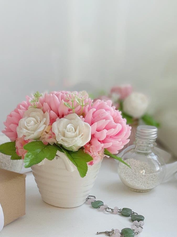 Mazzo delle rose e della bottiglia cosmetica su fondo bianco fotografia stock libera da diritti